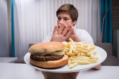 Man Refusing Unhealthy Food Offered By A Person