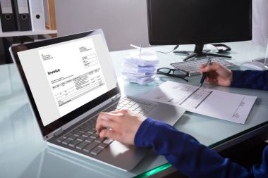 Close-up Of A Businessperson's Hand Checking Invoice On Laptop In Office