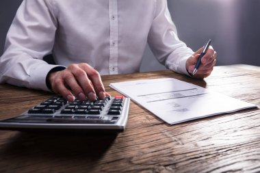 Businessperson's Hand Calculating Bill With Calculator On Wooden Desk