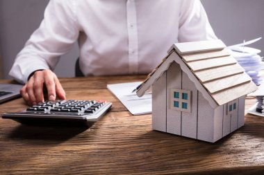 Wooden House Model In Front Of Businessperson Calculating Invoice