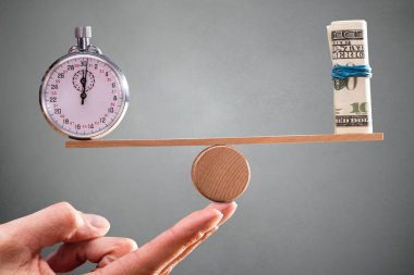 A Person Hand With Balance Between Stopwatch And Rolled Up Banknotes On Seesaw