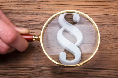 Businessperson's Hand Holding Magnifying Glass Over Paragraph Symbol On Wooden Desk