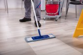 Fotografie Cleaner Cleaning Hardwood Floor With Mop At Workplace