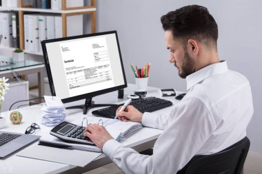 Young Businessman Calculating Invoice With Calculator At Desk
