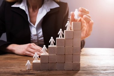 Businessperson's Hand Placing Human Figures On Staircase Made Up Of Wooden Blocks