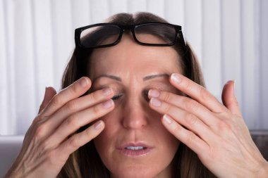 Close-up Of Woman With Eyeglasses Over Her Head Covering Her Eyes With Hand