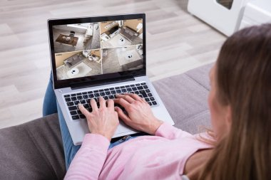 Close-up Of Woman Sitting On Couch Monitoring Home Security Cameras On Laptop At Home