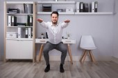 Fotografie Portrait Of A Happy Young Businessman Doing Workout In Office