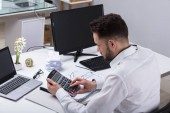 Young Businessman Calculating Bill With Calculator At Workplace