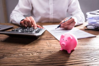 Businessperson Calculating Bill With Small Piggybank On Wooden Desk