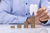 Fotografie Mann, die Münze auf den Stapel Münzen vor weißer Zahn platzieren