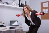 Smiling Mature Businesswoman Exercising With Red Dumbbell In Office