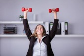 Portrait Of A Smiling Businesswoman Doing Exercise With Dumbbells