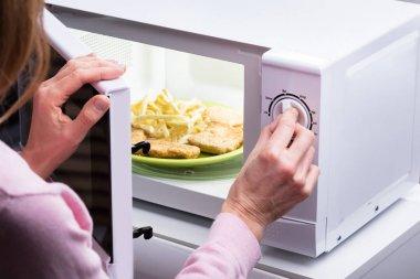 Photo Of Woman's Hands Opening Microwave Oven Door
