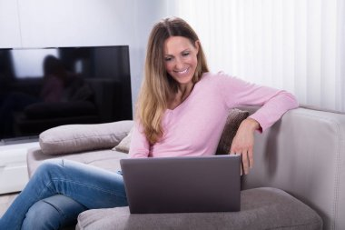 Happy Mature Woman Sitting On Sofa Using Laptop At Home