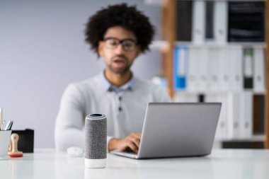 Close-up Of Young Businessman Speaking On Wireless Speaker At Workplace