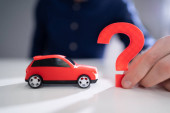 Person Hand Holding Question Mark Next To Car Model
