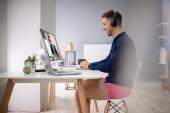 junger Geschäftsmann mit Kopfhörer bei Videokonferenzen am Computer