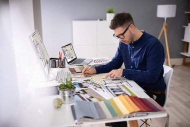 Side View Of Real Estate Designer Working On Computer In Office stock vector