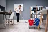 Hausmeister wischt Fußboden im Büro ab