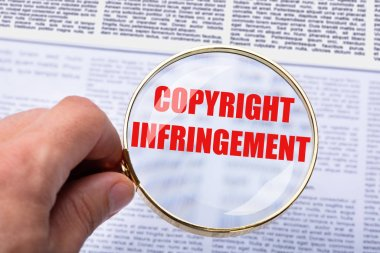 Close-up Of A Person's Hand Holding Magnifying Glass Over Copyright Infringement Word In Documents