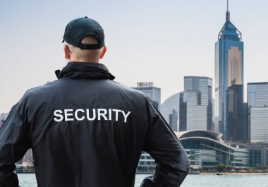 Rear View Of Male Security Guard Looking At City Skyline In Wan Chai District