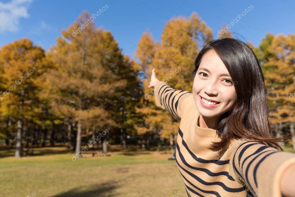 Woman taking photo in autumn season