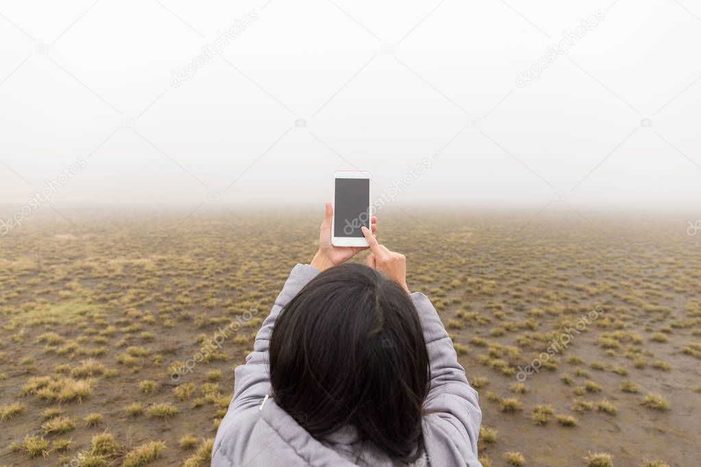 Back view of woman taking photo with fog