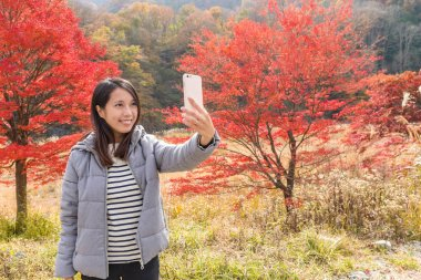 Woman taking photo on cellphone with maple trees