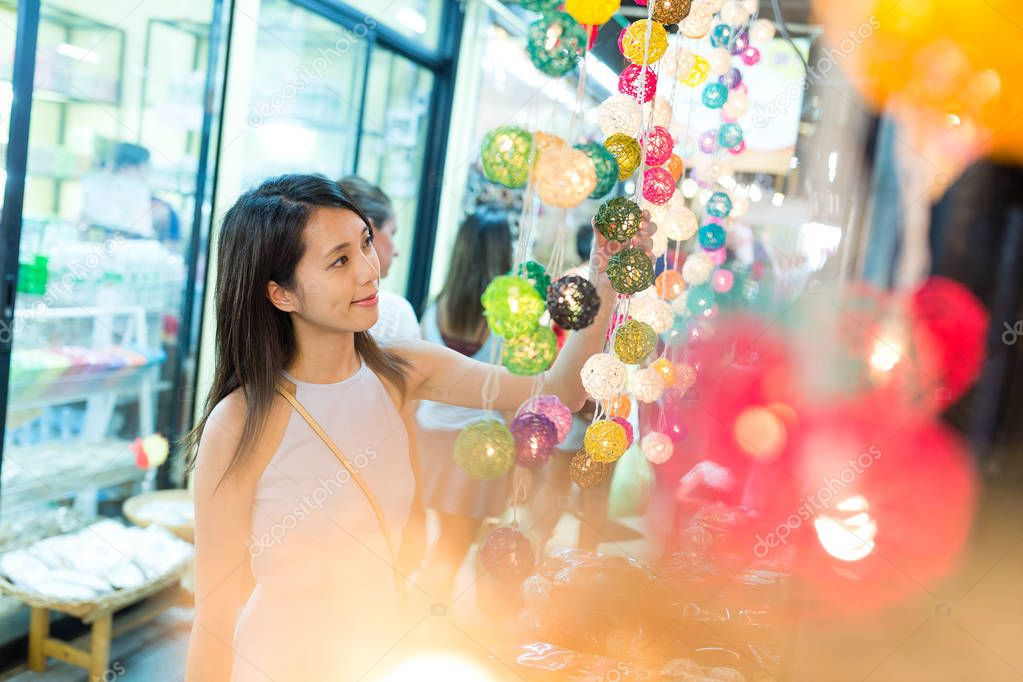 Woman shopping at decoration lantern in street market