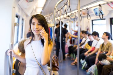 Woman talking on cellphone inside train compartment