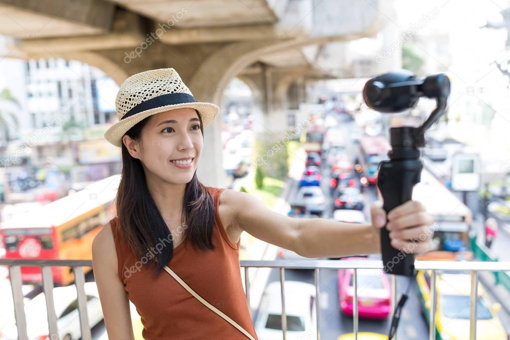 Woman holding video stabilizer to take video