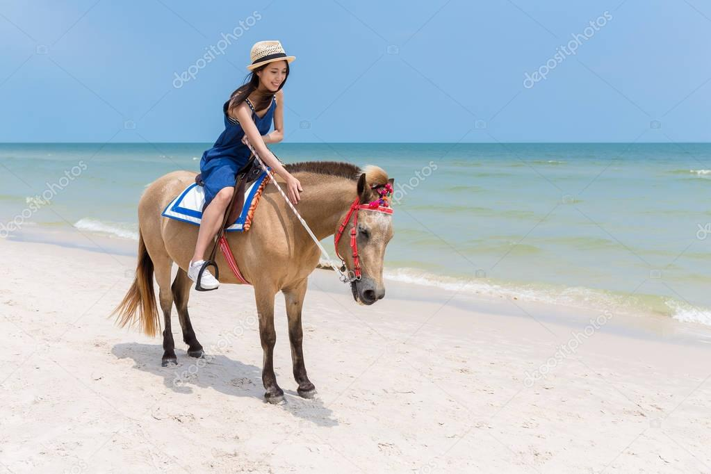 Woman riding horse on sand beach