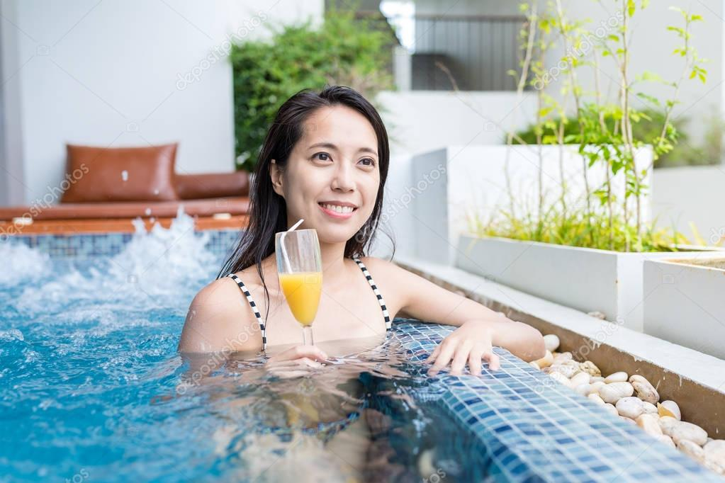 Woman enjoy her drink in swimming pool