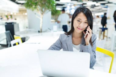 Businesswoman using notebook computer and talking on mobile phone