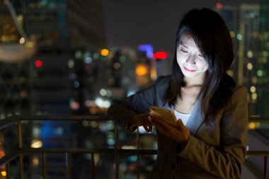 Businesswoman using mobile phone at night