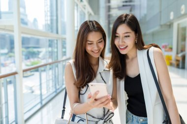 girls go shopping together and using mobile phone