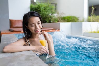 Woman in jacuzzi pool and enjoy juicy drink