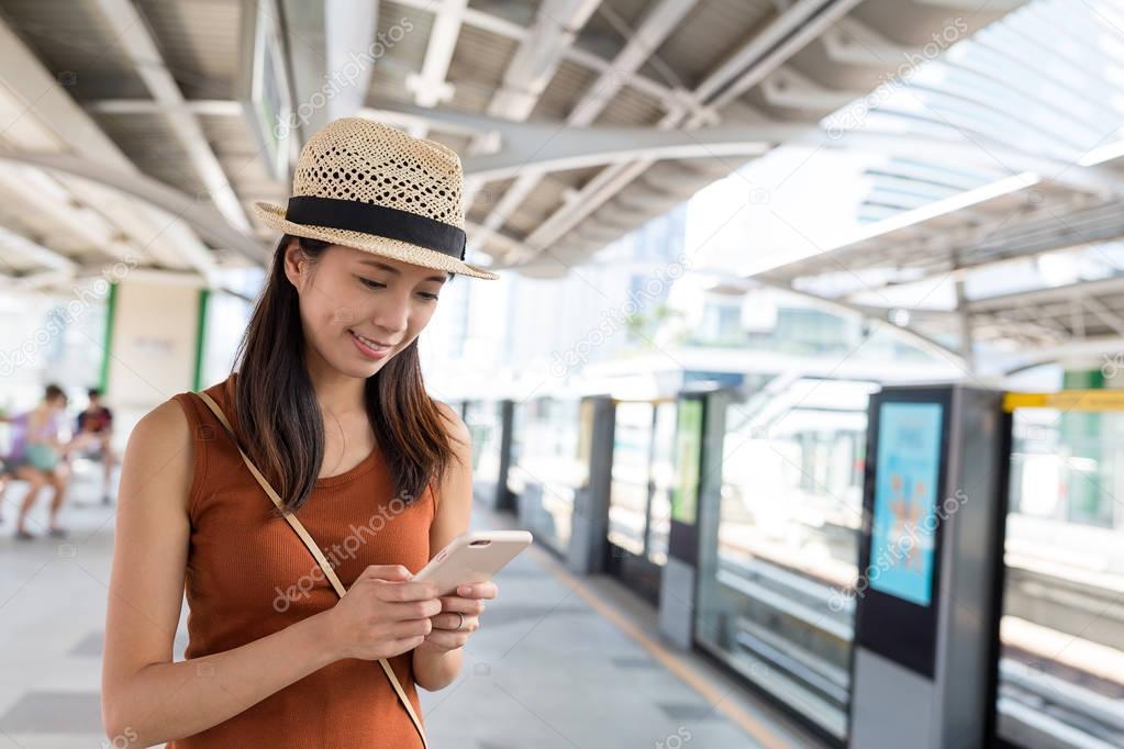 Woman using cellphone on train platform