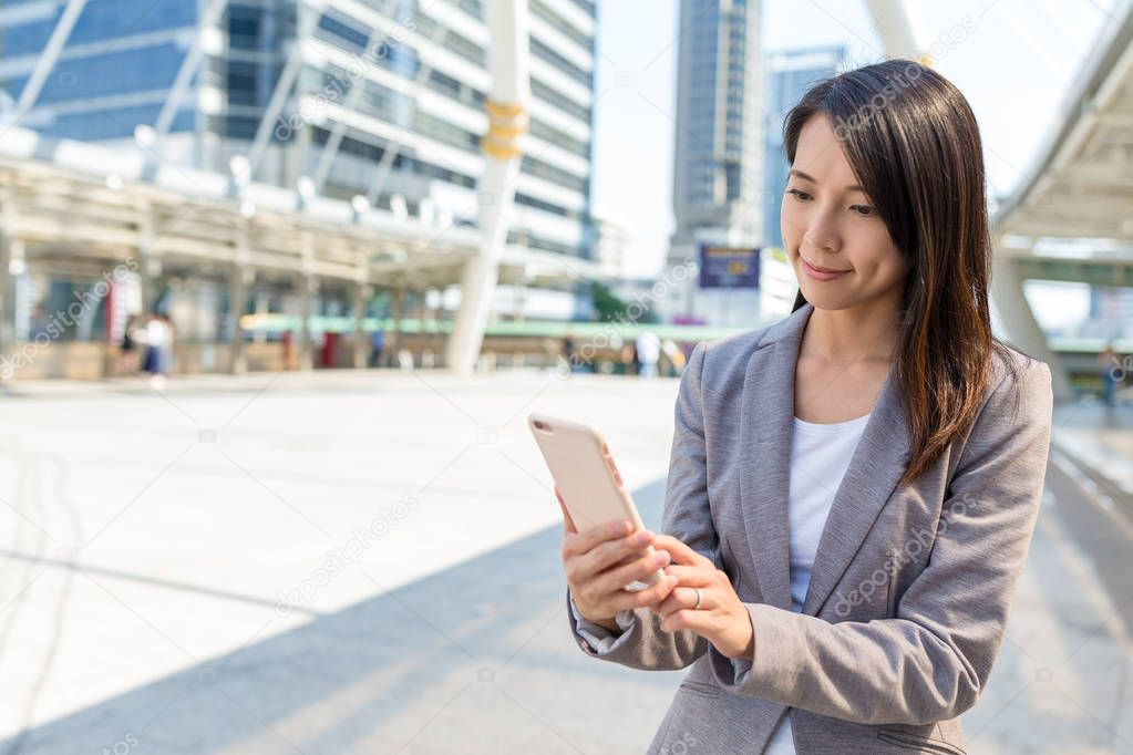 Businesswoman sending sms on mobile phone