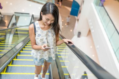 Woman using mobile phone on escalator