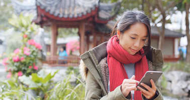 Woman using mobile phone in Chinese garden