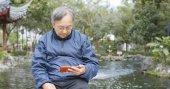 Fotografie Asiatischer senior Mann gerade auf Handy im chinesischen Garten