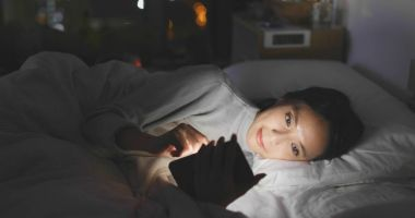 Woman using smartphone and lying on bed at night
