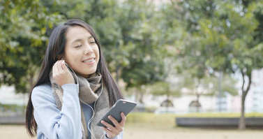 Woman listen to music on cellphone at outdoor