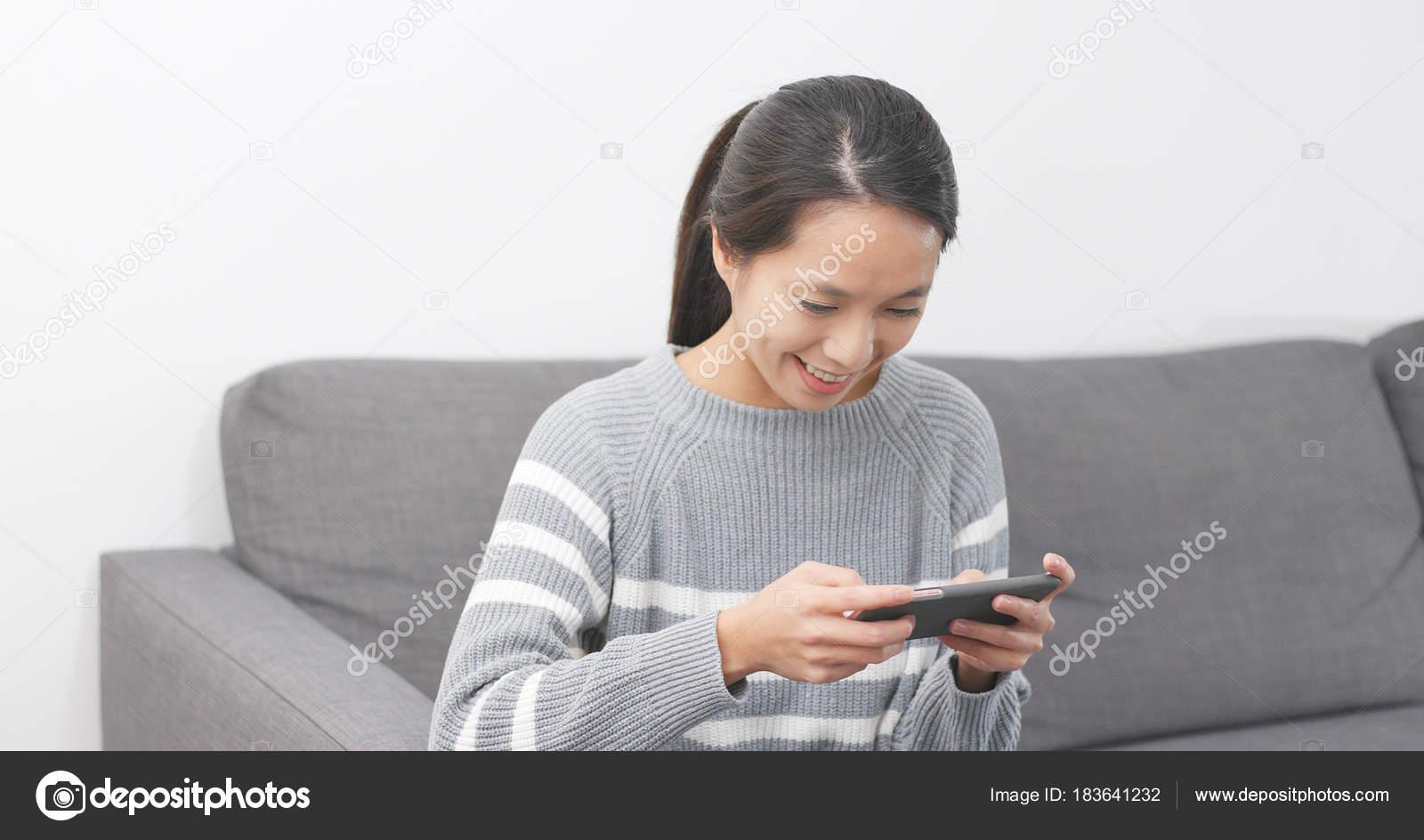 Толстяк в желтой рубашке доволен собой держа телефон с зеленым.