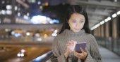 Fotografie Frau mit Smartphone in der Stadt bei Nacht