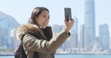 Woman taking video call on cellphone in Hong Kong city
