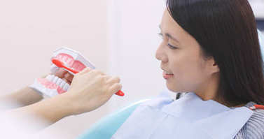 Dentist showing patient how to brush teeth