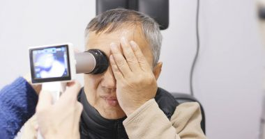 Old man checking on eye stock vector